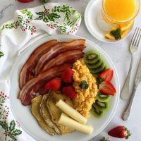 Ovos mexidos com bacon, queijo fatiado, batata-doce, fruta e sumo natural de laranja